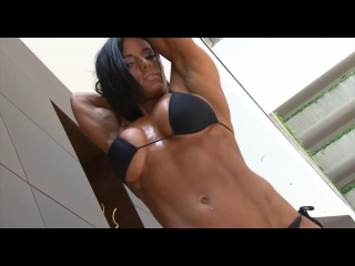 Beautiful fitness cute girl with huge boobs flexing her muscles